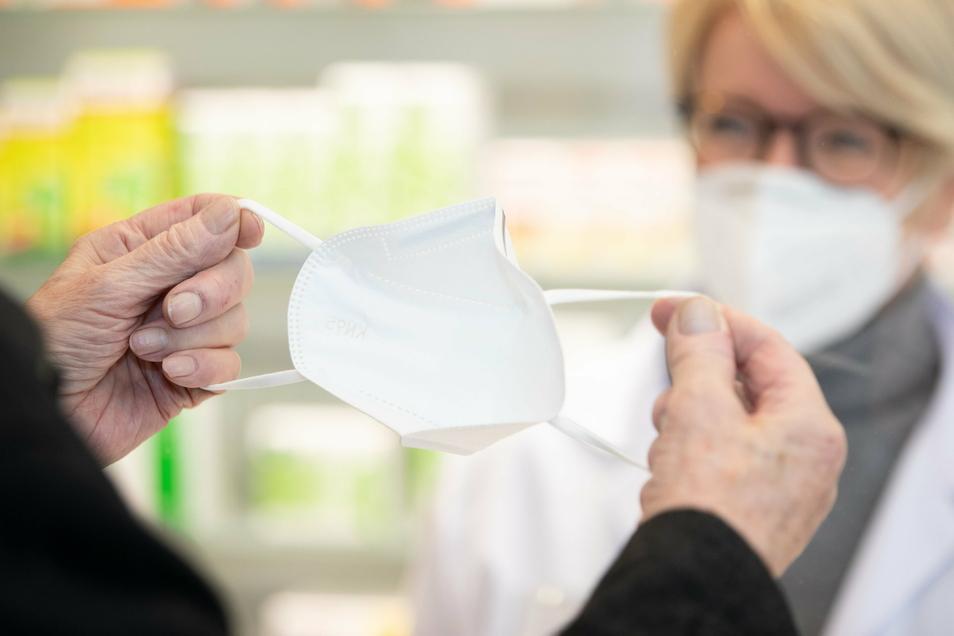 Eine Apothekerin gibt einem älteren Kunden eine FFP2-Mund- und Nasenschutzmaske.