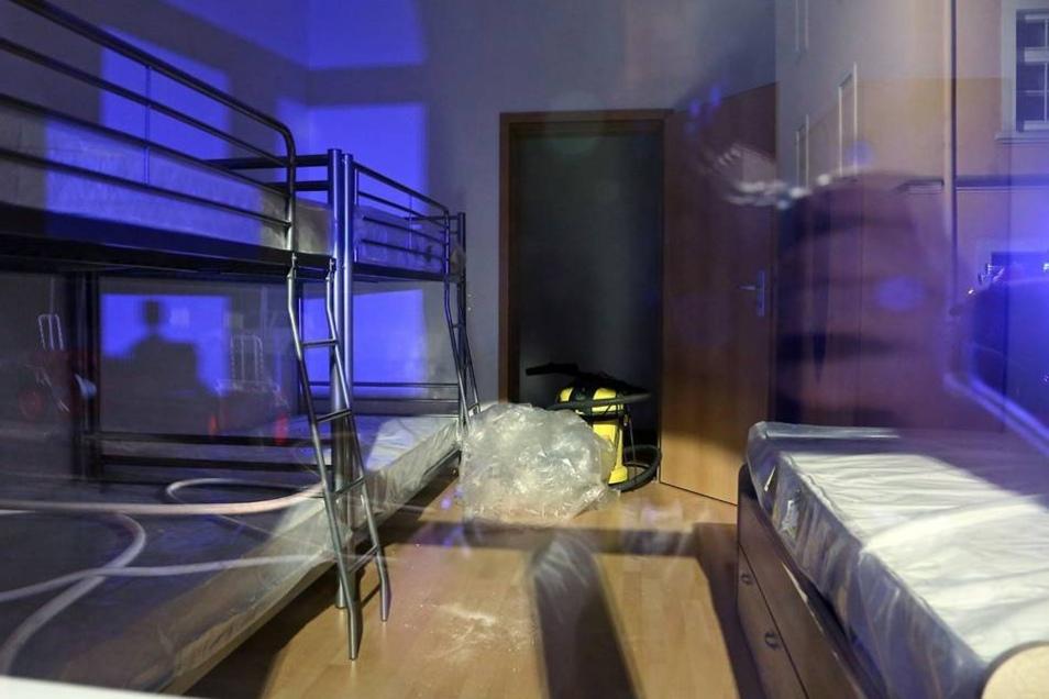 Der Blick durch ein Fenster im Erdgeschoss in ein neu eingerichtetes Zimmer.