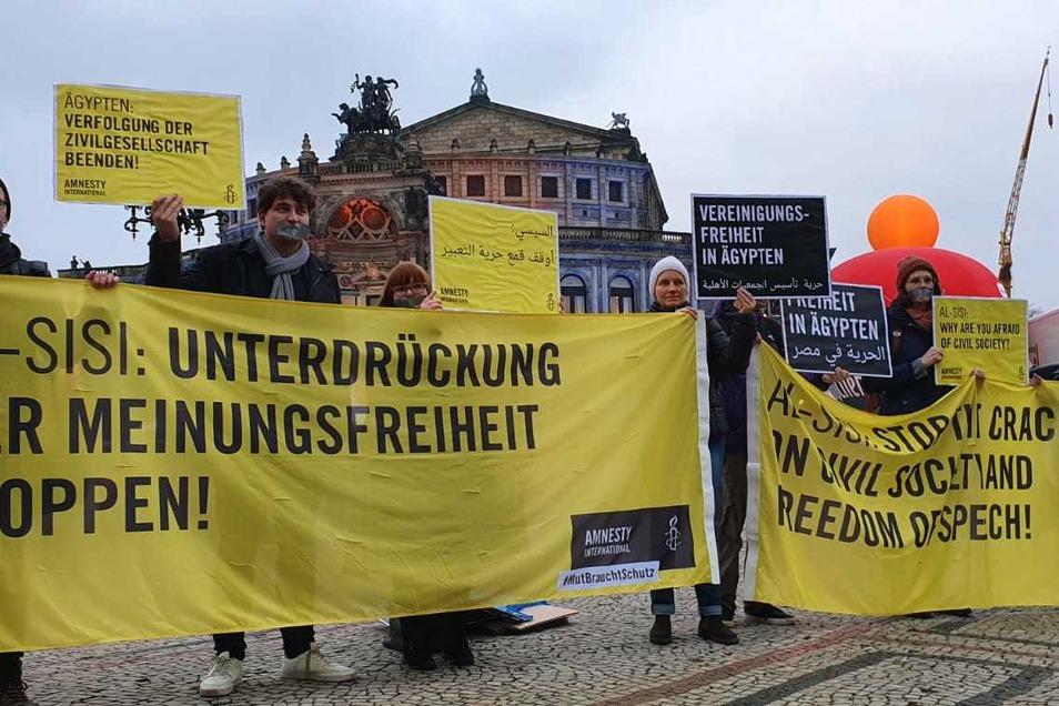 Mitglieder von Amnesty International demonstrieren vor der Semperoper gegen die Verleihung des St.-Georgs-Ordens an al-Sisi.