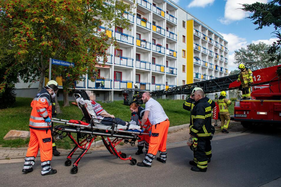 Eine Bewohnerin hat gesundheitliche Probleme und wird nach ihrer Rettung vom Balkon vom Rettungsdienst in Empfang genommen.