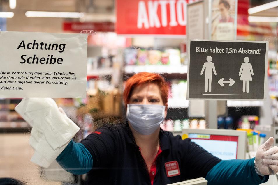"""Ein Mitarbeiterin in einem Dresdner Supermarkt putzt einen sogenannten """"Spuckschutz"""" an der Kasse.Das neuartige Coronavirus wird vor allem durch Tröpfcheninfektion übertragen."""