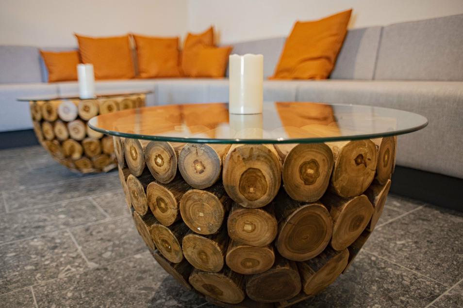 Originelle Tische stehen bei den Sofas vor den Saunen.