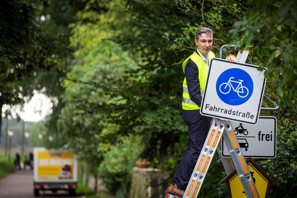 """Baubürgermeister Stephan Kühn hat am Freitag das letzte """"Fahrradstraße""""-Schild am Kleinzschachwitzer Ufer selbst angebracht."""