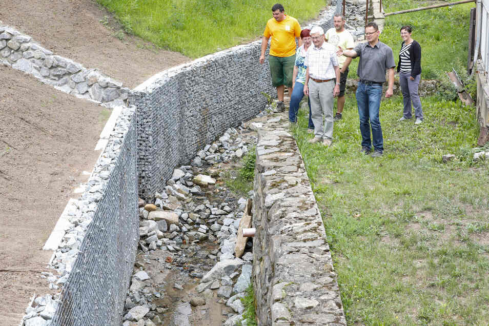 Die Stützmauer in Spitzkunnersdorf ist fertig. Bürgermeister Bruno Scholze besichtigte mit Bauleuten und Kollegen aus der Verwaltung das fertige Bauwerk.