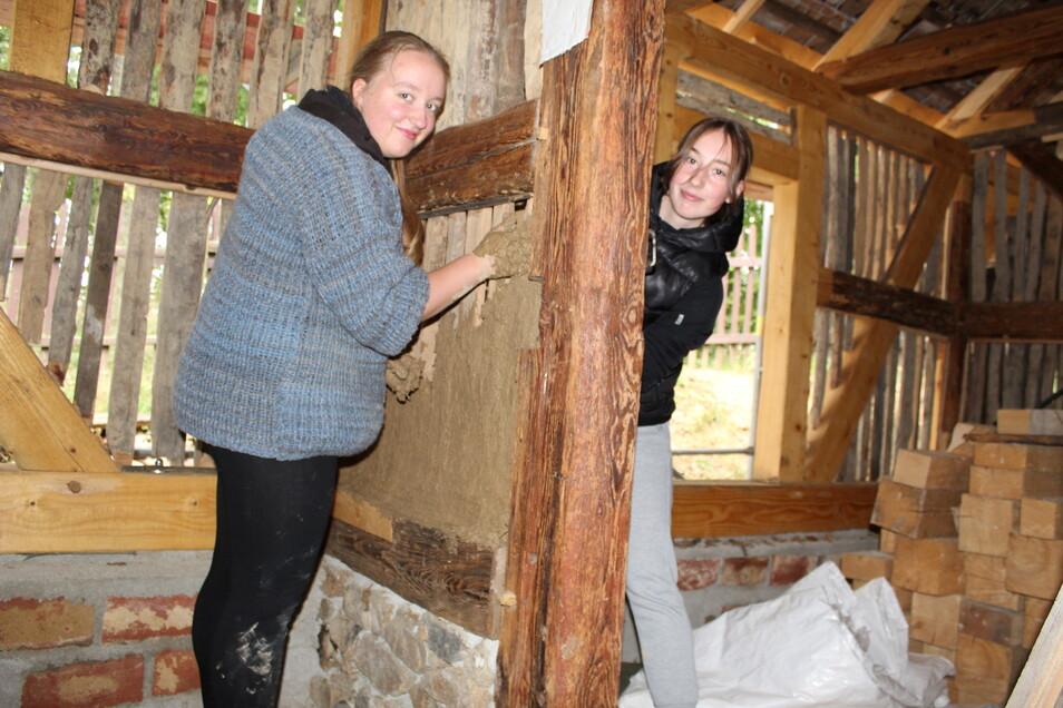 Nele Beitlich (l.) und Karolin Simon aus der Paulusschule in Königswartha helfen beim Ausfachen mit Lehm im wiederaufgebauten Scharfrichterhaus in Luga.