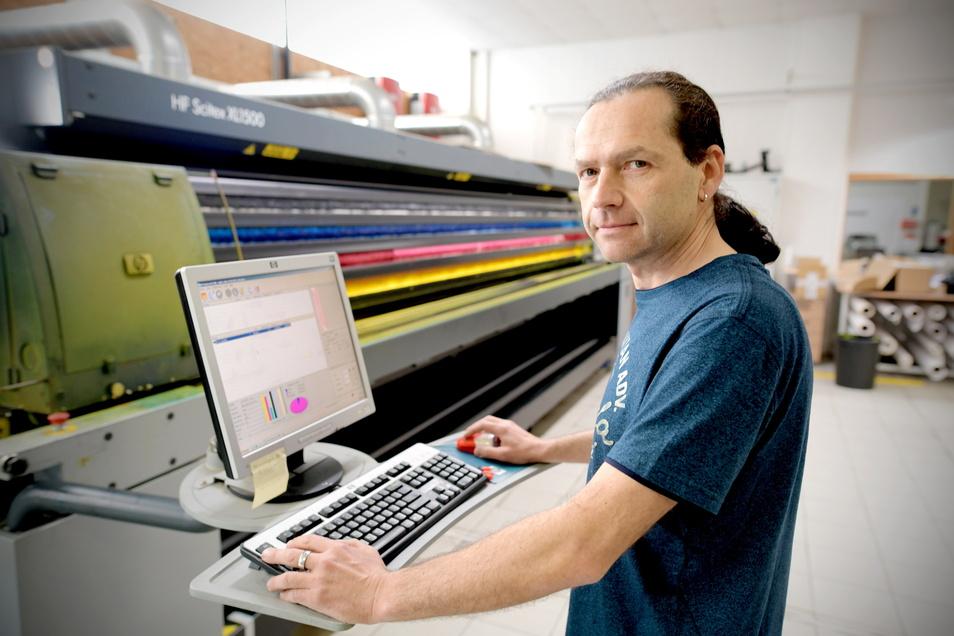 Geschäftsführer Andreas Wagner an einer großen digitalen Druckmaschine, wo sonst Werbebanner für Messebauer, Veranstalter und Eventagenturen hergestellt werden.