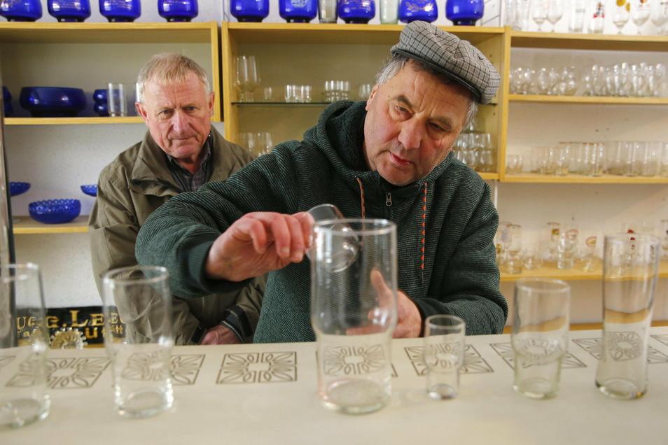 Uwe Jähnig zeigt die superfesten Gläser im DDR-Museum in Schwepnitz. Im Hintergrund Peter Sonntag. Er war mit dafür verantwortlich, dass die Produktion im Ort in den 1980er-Jahren anlief.