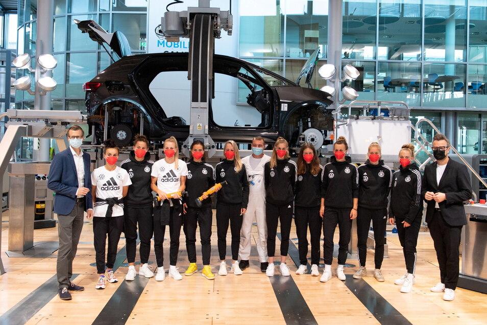 Die Spielerinnen der Frauenfußball-Nationalmannschaft stehen in der Gläsernen Manufaktur neben Danny Auerswald (l), dem VW-Standortleiter, vor einem Volkswagen ID.3.