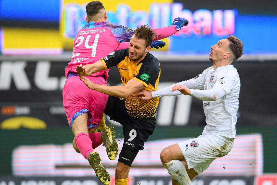 Bei diesem Zusammenprall mit Ingolstadts Torwart Fabijan Buntic (l.) hat sich Dynamos Stürmer Pascal Sohm eine Hüftprellung zugezogen; Tobias Schröck beobachtet die Szene.