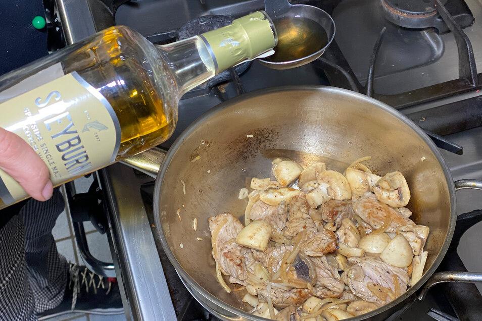 Whisky in einer Kelle entzünden, in die Pfanne gießen und sofort alles schwenken.
