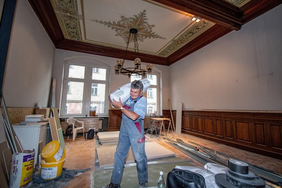 Jürgen Hofmann von der Döbelner Ausbau und Modernisierungs GmbH schleppt hier noch Baumaterial durch die künftige Garderobe der Kita-Kinder.