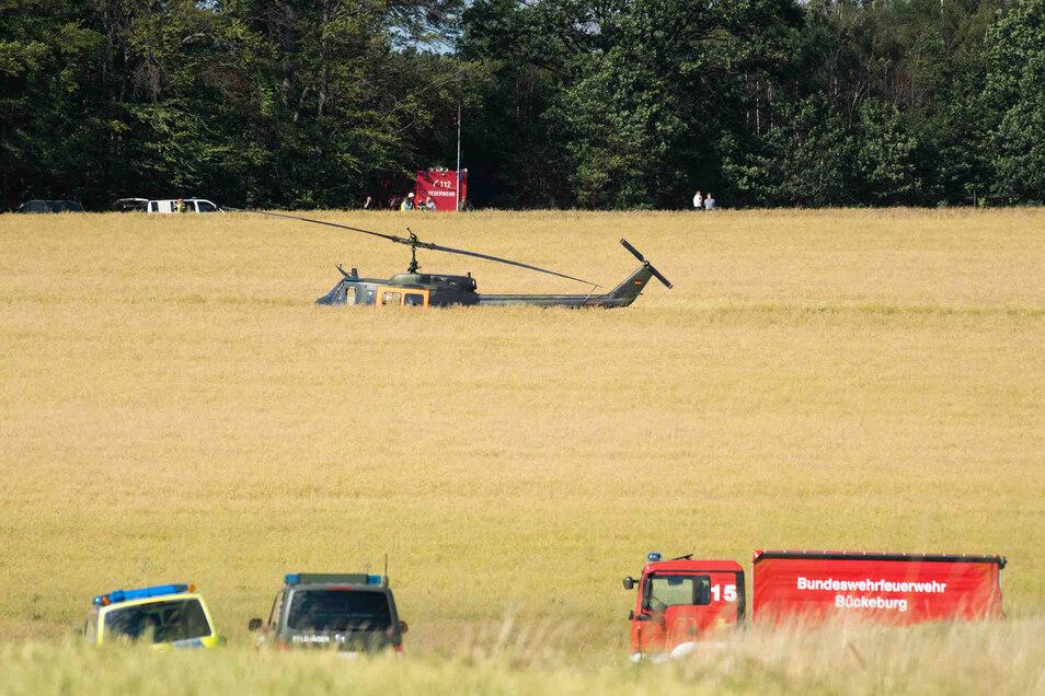 Einsatzfahrzeuge und ein Hubschrauber der Bundeswehr stehen nahe einer Absturzstelle an einem Feld.