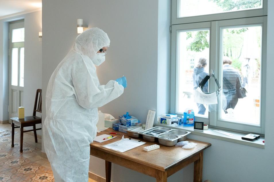 Janine Keith steht im Corona-Testzentrum in der Dresdner Sommerwirtschaft Neue Welt Paul Rackwitz und bereitet einen Corona-Schnelltest vor.