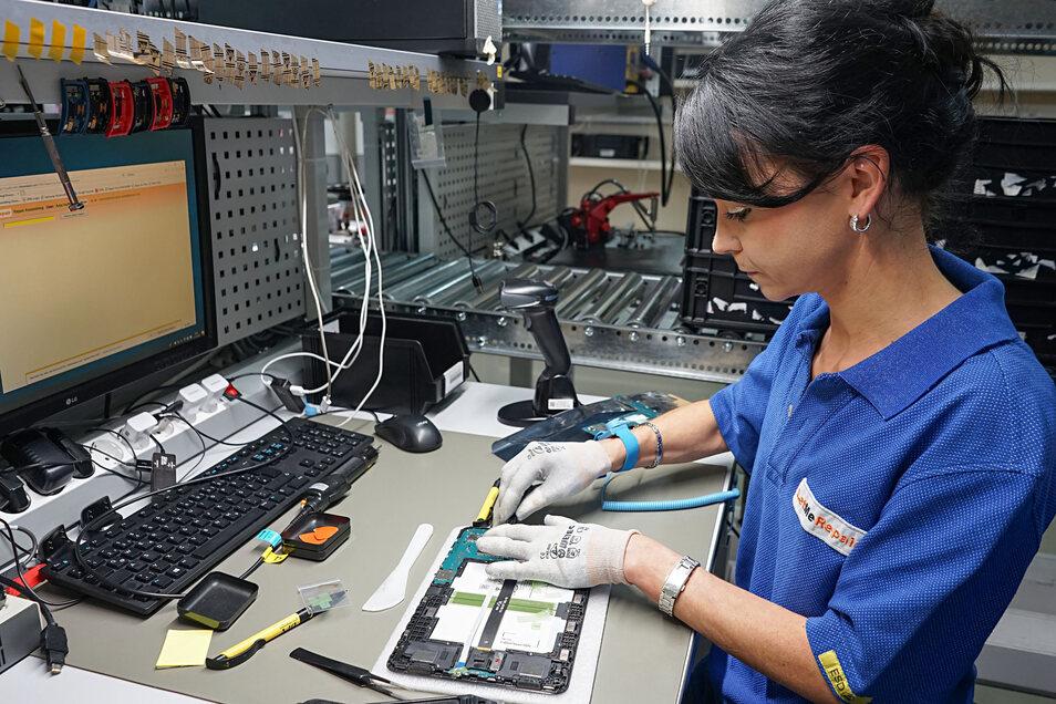 Mit wenigen Handgriffen bringt Anja Hoffmann ein defektes Tablet in Ordnung. Sie gehört zu den rund 50 Mitarbeitern, die in der Kirschauer Betriebsstätte der Firma LetMeRepair elektronische Geräte – vor allem Handys und Tablets – reparieren.