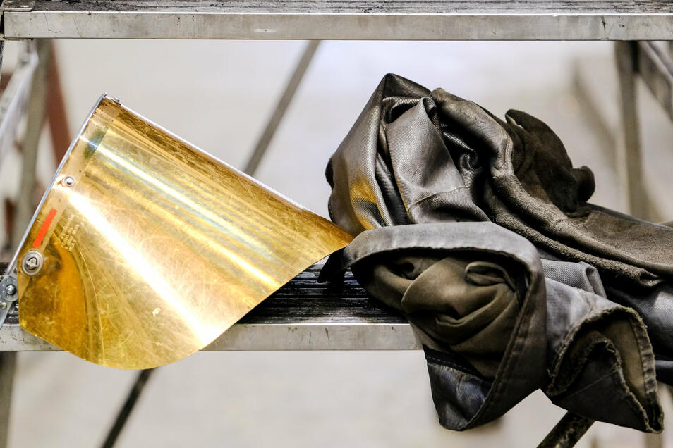 Stillleben mit Gesichtsschutz und Schutzjacke. Beides wird von den Arbeitern in der Gießerei getragen, wenn das etwa 1.300 Grad heiße Metall in die Formen gegossen wird. Insgesamt 40.000 Tonnen Eisenguss im Jahr werden in der Walze Coswig produziert.