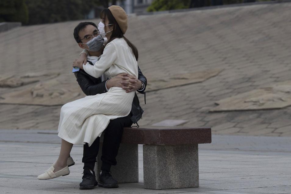 Ein Paar mit Mundschutz sitzt zusammen auf einer Bank in Wuhan. Von den mehr als 81.000 offiziell gemeldeten Infektionen in China waren 50.000 allein in Wuhan.