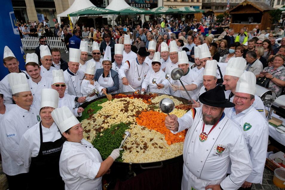 Köche des Internationalen Kochkunstvereins zu Leipzig stehen auf dem Marktplatz um eine Pfanne herum. Die Köchinnen und Köche versuchten, die größte Portion des Traditionsgerichtes ·Leipziger Allerlei· zuzubereiten.