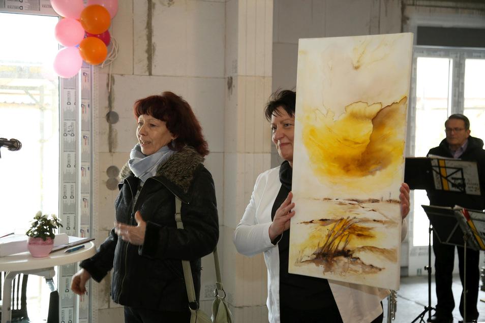 Gabriele Beinlich (links) stellt das erste Gemälde für die Hilfsaktion der Nieskyer Freizeitkünstler vor. Hospiz-Bauherrin Sonja Rönsch ist begeistert.