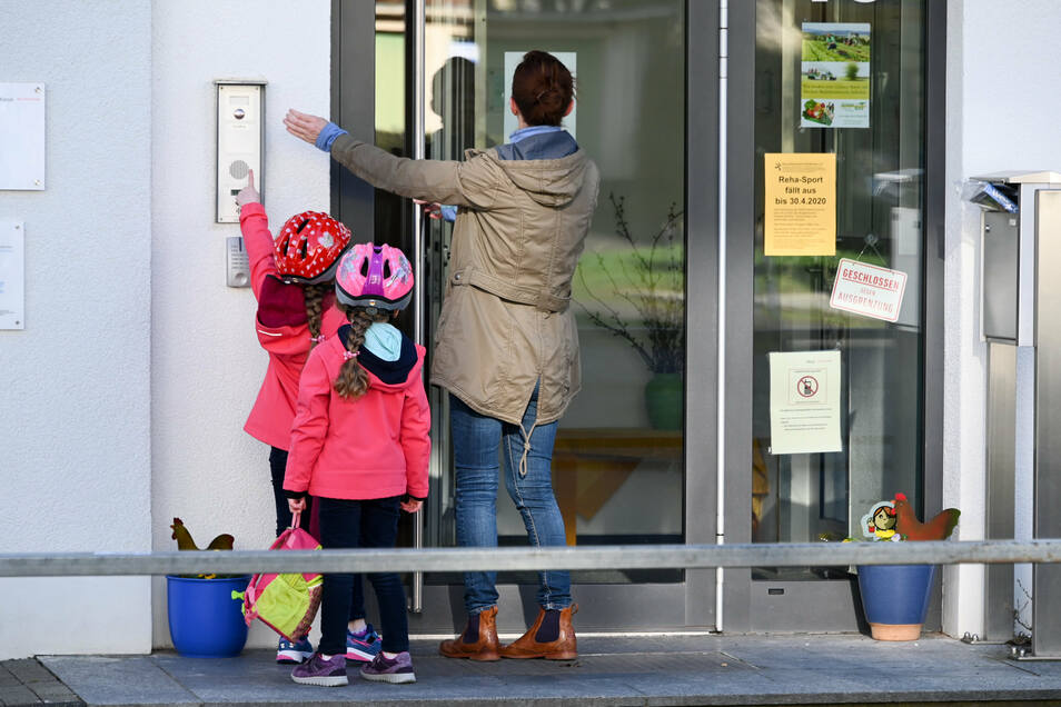 Eine Mutter steht mit ihren Kindern vor dem Kita-Eingang und klingelt.