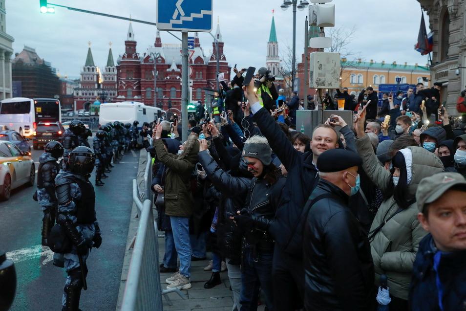Polizisten stehen in Moskau Demonstranten gegenüber, die während eines Protests zur Unterstützung des inhaftierten Oppositionsführers Nawalny ihre leuchtenden Handys in die Höhe halten.