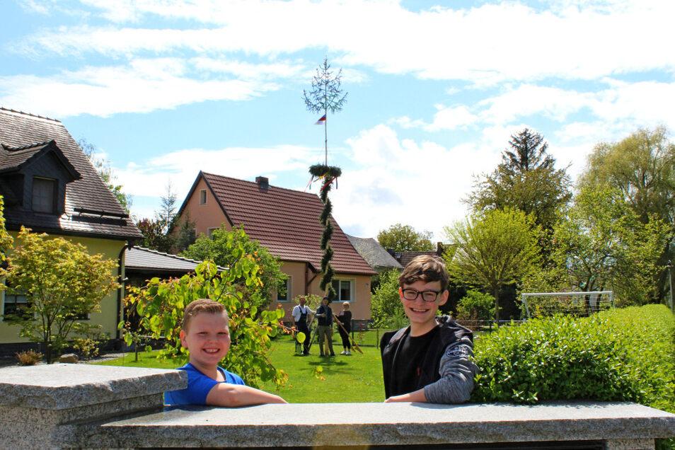 Lukas Kummer (links) und Tobias Crüger (rechts) sowie Daniel und Susann Kummer und Paul Graf vom Jugendclub (Bildmitte) freuen sich über die besondere Aktion des Maibaumstellens. Im Garten von Kummers steht dieses Exemplar.