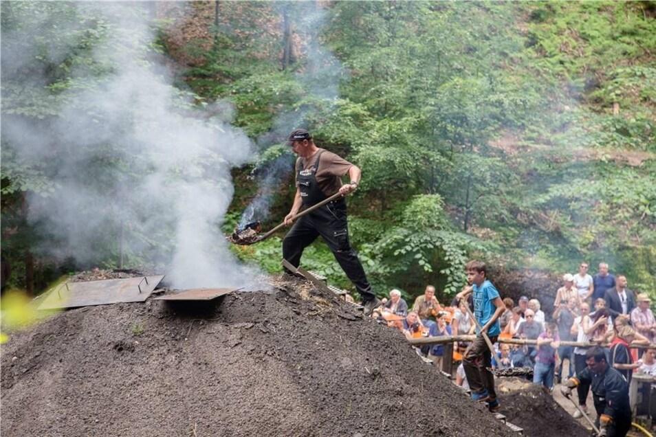 Bei der Hitze am Sonnabend war es eine schweißtreibende Angelegenheit, den Meiler im Tharandter Wald zu entzünden. Das Spektakel, zu dem der Meilerverein Tharandt eingeladen hatte, verfolgten viele Besucher.