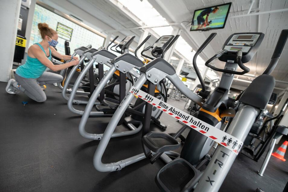 Auf Distanz: Die Angestellte eines Fitnessstudios befestigt ein Absperrband an einem Gerät.