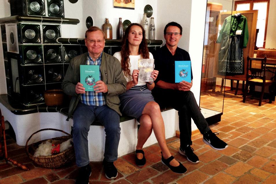 Wo Geschichten erzählt werden: Thomas Delling (links), Carolin Eberhardt und Tobias Zschieschick mit den Neu-Büchern auf der Ofenbank in der Trachtenstube.