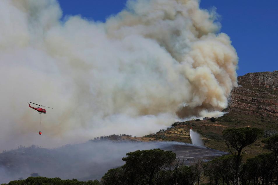 Ein Helikopter wirft Wasser über einem Brand auf dem Tafelberg ab. Ein Großfeuer in Südafrikas Touristenmetropole Kapstadt hat erhebliche Flächen des berühmten Tafelbergs in Mitleidenschaft gezogen.