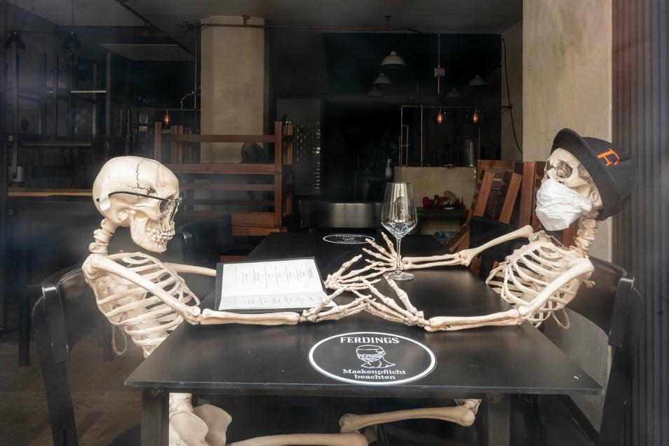 Zwei Skelette sitzen sich in der Auslage eines geschlossenen Lokals in der Innenstadt von München an einem Tisch gegenüber.