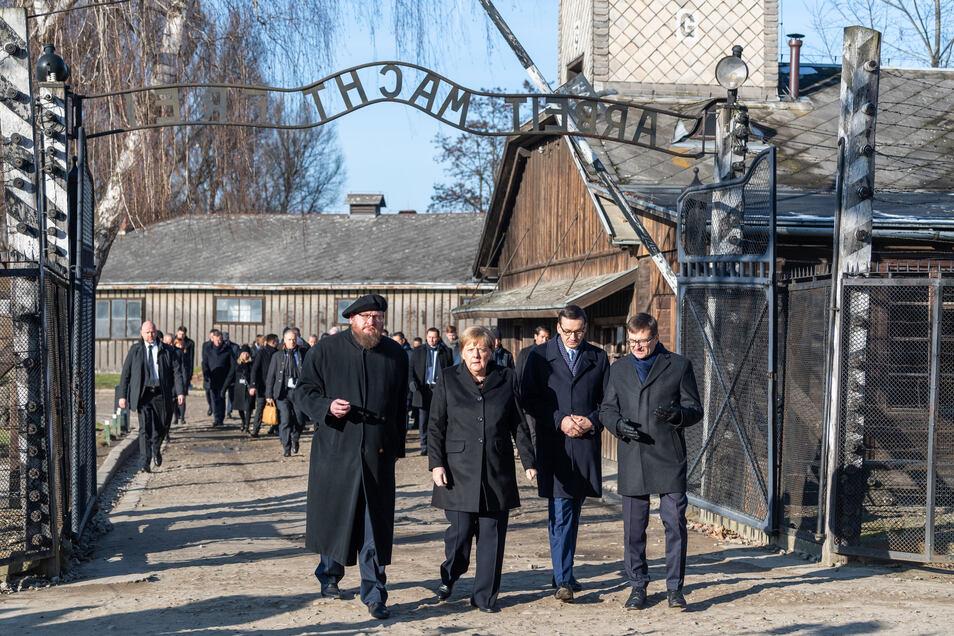 Angela Merkel zusammen mit dem polnischen Ministerpräsidenten Mateusz Morawiecki (rechts neben Merkel) und dem Direktor der Gedenkstätte und Präsidenten der Stiftung Auschwitz-Birkenau, Piotr Cywinski (links neben Merkel).