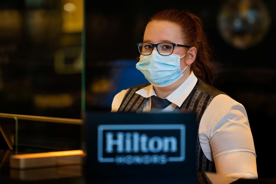 Hotelfachfrau Jenny Neumann sitzt trotzdem an der Rezeption und empfängt Gäste.