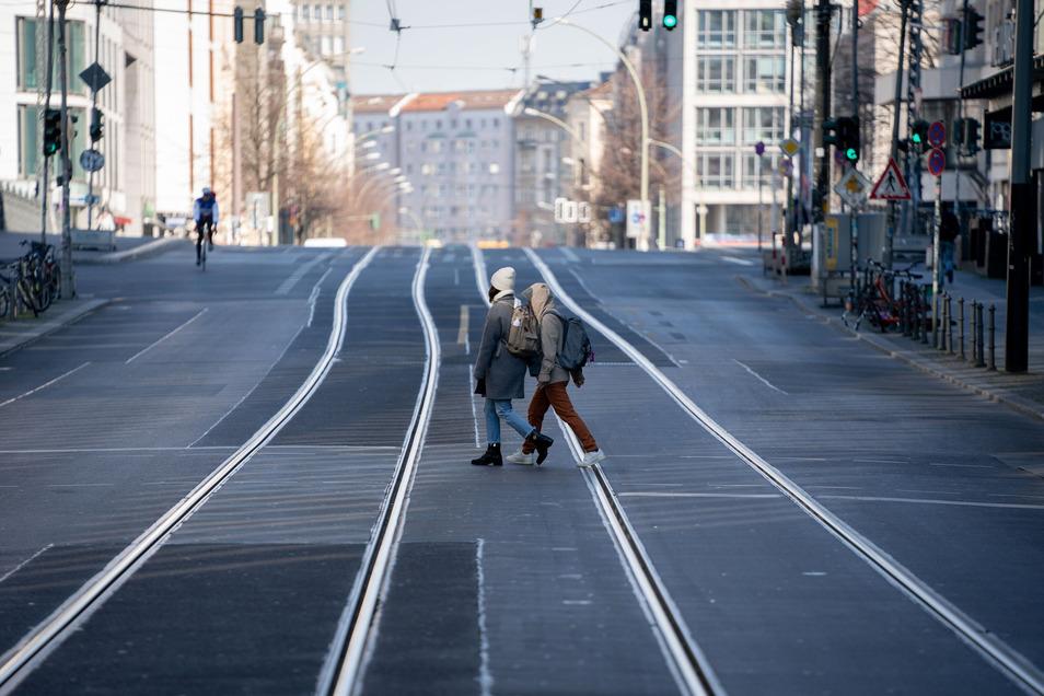 Passanten überqueren die nahezu unbefahrene Friedrichstraße in Berlin.