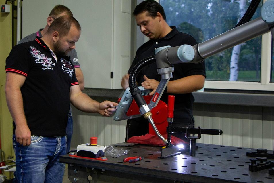 Markus Weiner (links) an einem Schweißroboter. Der Schweißfachingenieur prüft, ob der Roboter für Arbeiten in der Firma Metallbau einer in Ludwigsdorf geeignet ist.