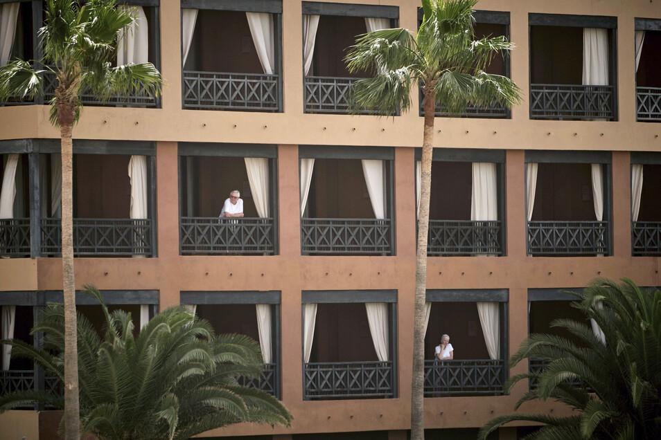 Hotelgäste stehen auf den Balkonen des Hotels H10 Costa Adeje Palace auf Teneriffa. Nach einem bestätigten Coronavirus-Fall ist das Hotel unter Quarantäne gestellt worden.