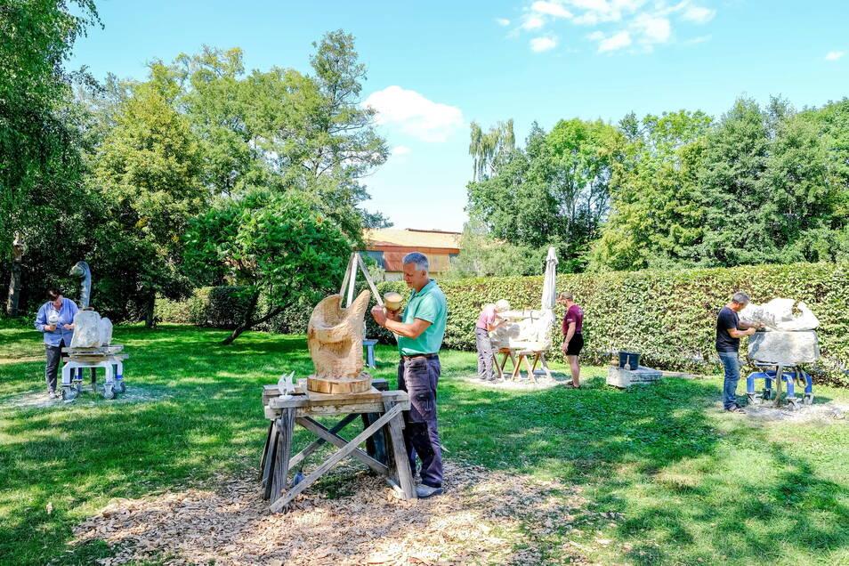 Beim Symposium 2019 wurde im Gelände von Adams Gasthof gearbeitet. Diesmal befindet sich die Freiluft-Werkstatt der Künstler nicht weit davon entfernt. Gleich hinter der Hecke, neben der Reithalle des Landgestüts.