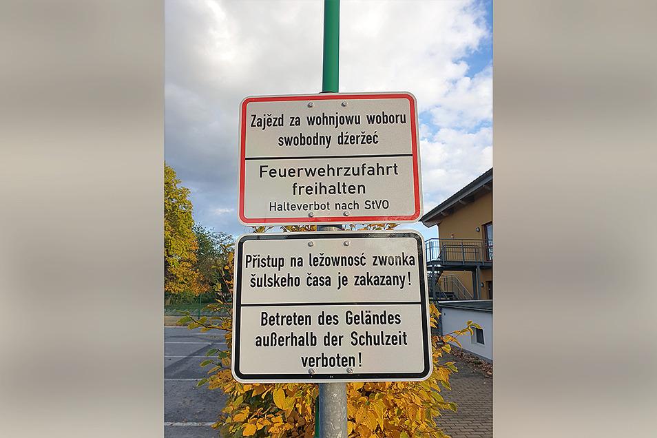 Ein positives Beispiel für zweisprachige Beschriftung sind diese nahezu identisch großen Hinweisschilder an der Schule in Ralbitz.