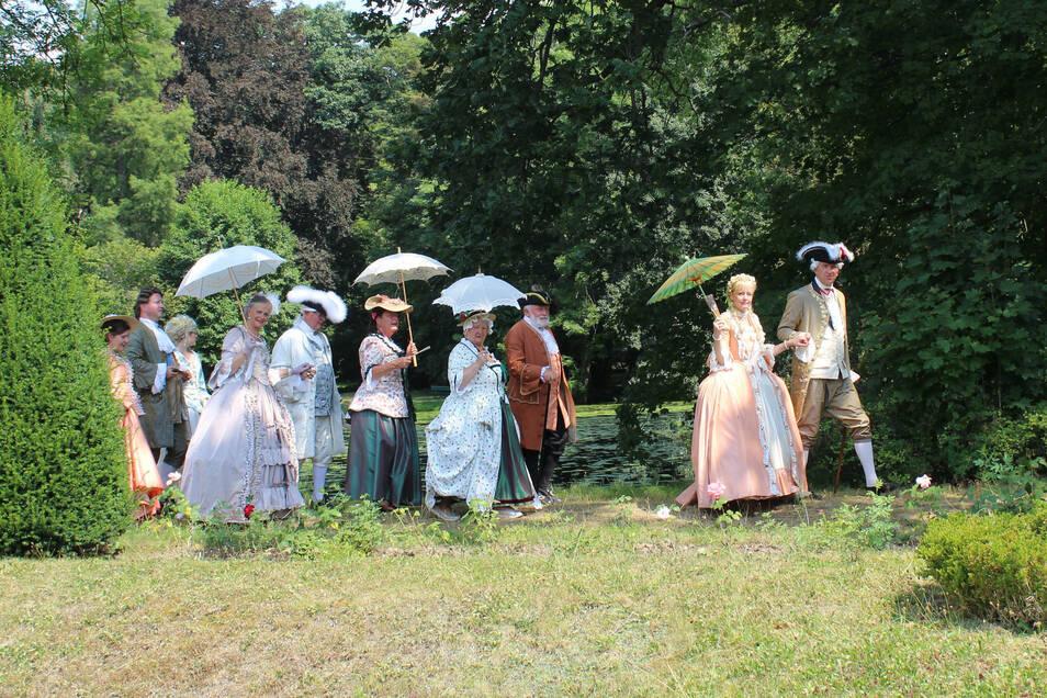 """Als die Mitglieder des Vereins """"Barock in Dresden"""" durch den Seußlitzer Schlosspark spazieren, werden viele Sonnenschirme aufgespannt."""