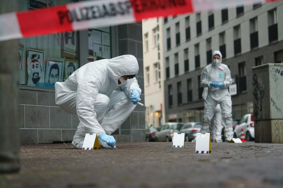 Beamte der Spurensicherung sichern Blutspuren auf dem Gehweg in Frankfurt/Main. Bei einer mutmaßlichen Messerattacke sind am Morgen mehrere Menschen verletzt worden.