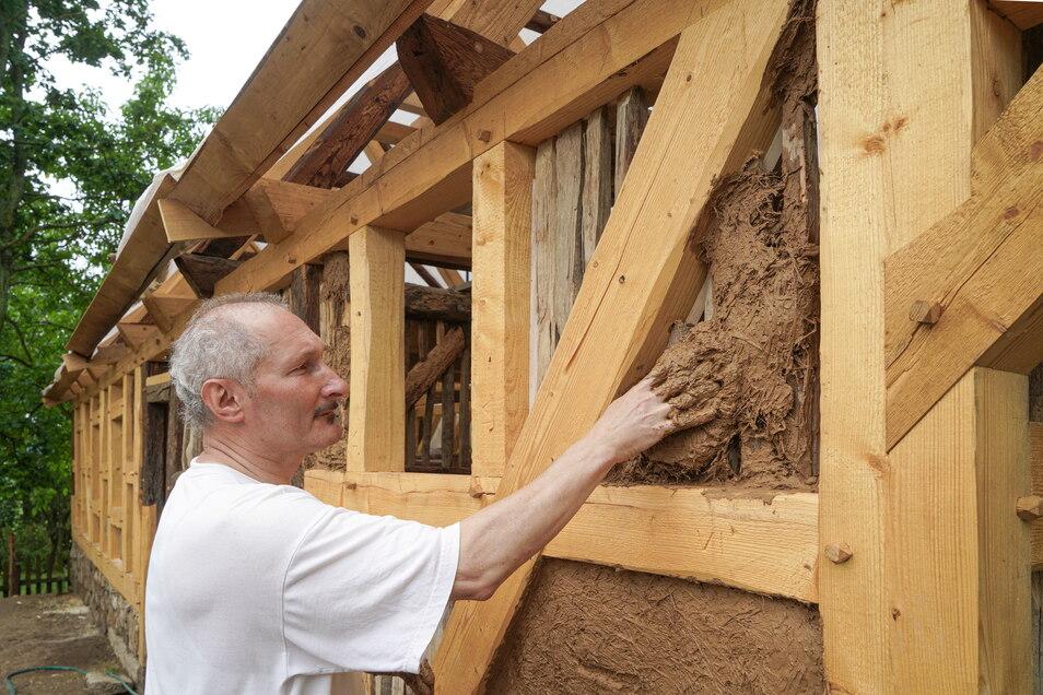 Eine vergnügliche Pamperei: Arnd Matthes von der Stiftung Umgebindehaus benutzt historischen Lehm, um die Gefache des geretteten Scharfrichterhauses am neuen Standort in Luga zu verputzen.