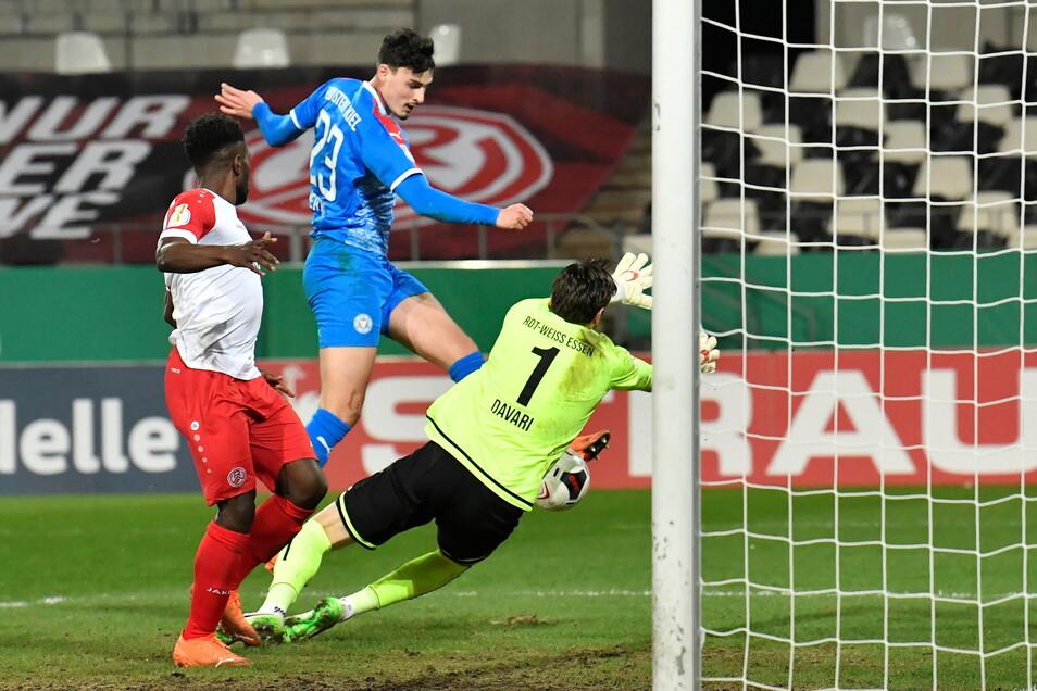 Kiels Janni Serra (2.vl) erzielt gegen die Essener Daniel Heber (l) und Torwart Daniel Davari das Tor zum 0:2.