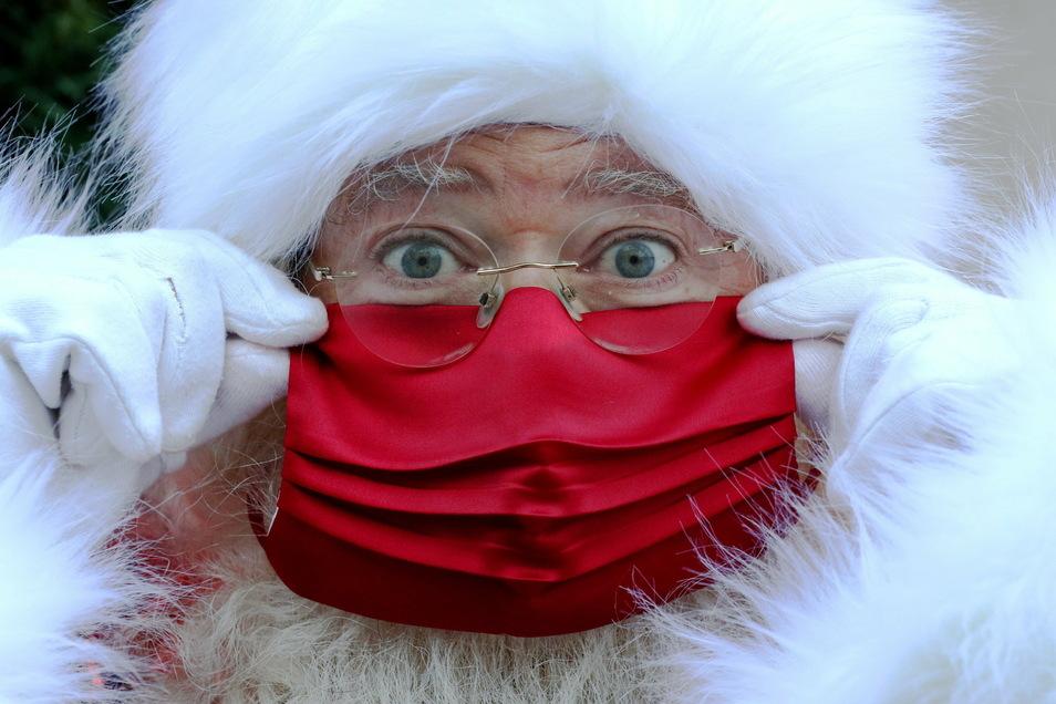 Korrekt! Auch der Weihnachtsmann trägt einen Mund-Nase-Schutz, wenn er am Sonnabend Kinder in der Altstadt von Pirna beschenkt.