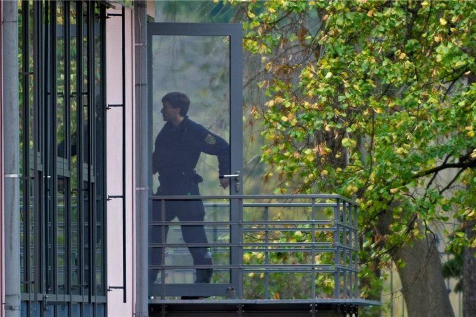 Ein Beamter auf einem Balkon der Villa auf der Käthe-Kollwitz-Straße.
