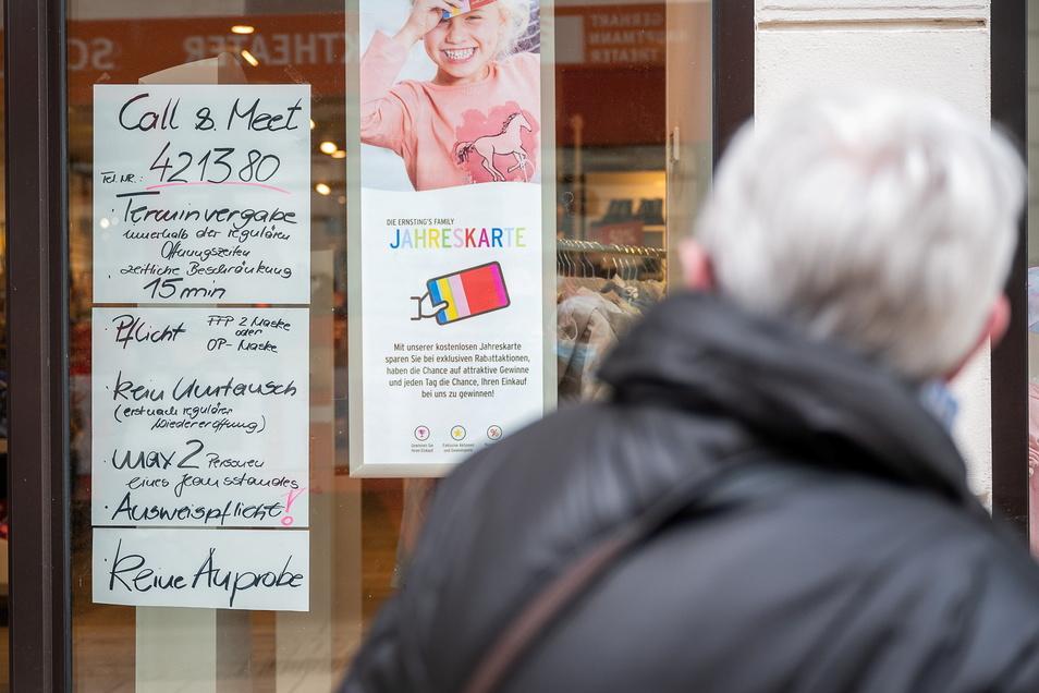Ein Kunde betrachtet die Einlassregeln vor einem Geschäft auf der Berliner Strasse in Görlitz.