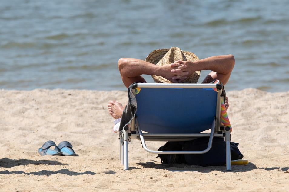 Ostseefeeling: Ein Mann liegt mit einem Sonnenhut auf einer Sonnenliege am Strand des Bärwalder Sees.