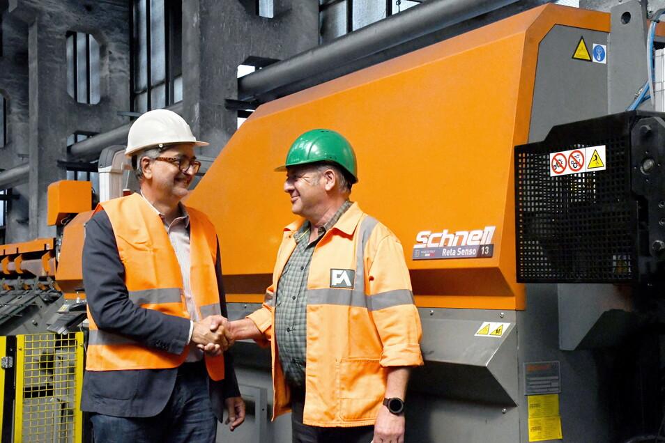 Auf gute Zusammenarbeit: Simone Rupoli vom Unternehmen Schnell spa (li.) übergibt die neue Maschine an Bernd Kalies, den Betriebsdirektor Drahtwerk bei Feralpi Stahl.