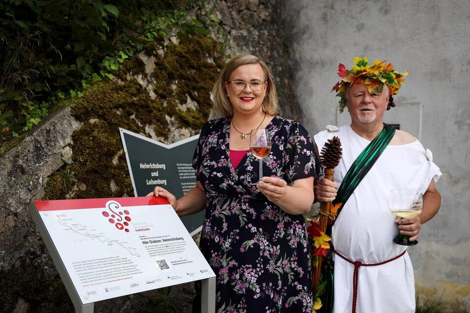 Maria Lehmann steht mit Bacchus neben der neuen Audio-Guide-Tafel an der Heinrichsburg in Diesbar-Seußlitz.