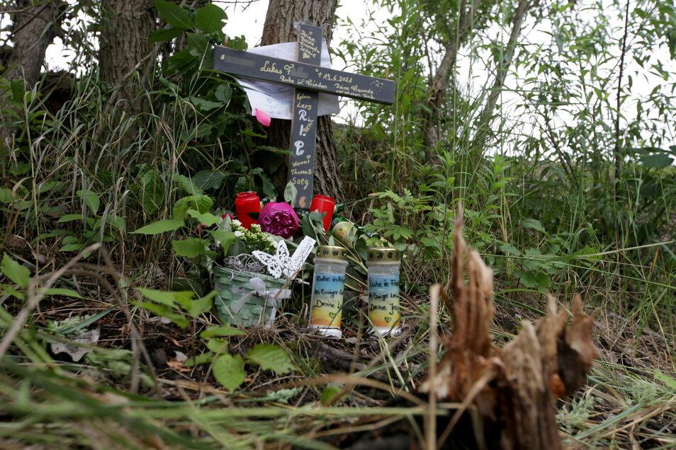 Am Kiessee in Dresden-Zschieren haben Freunde des ertrunkenen jungen Mannes ein Holzkreuz, Blumen und Kerzen aufgestellt.