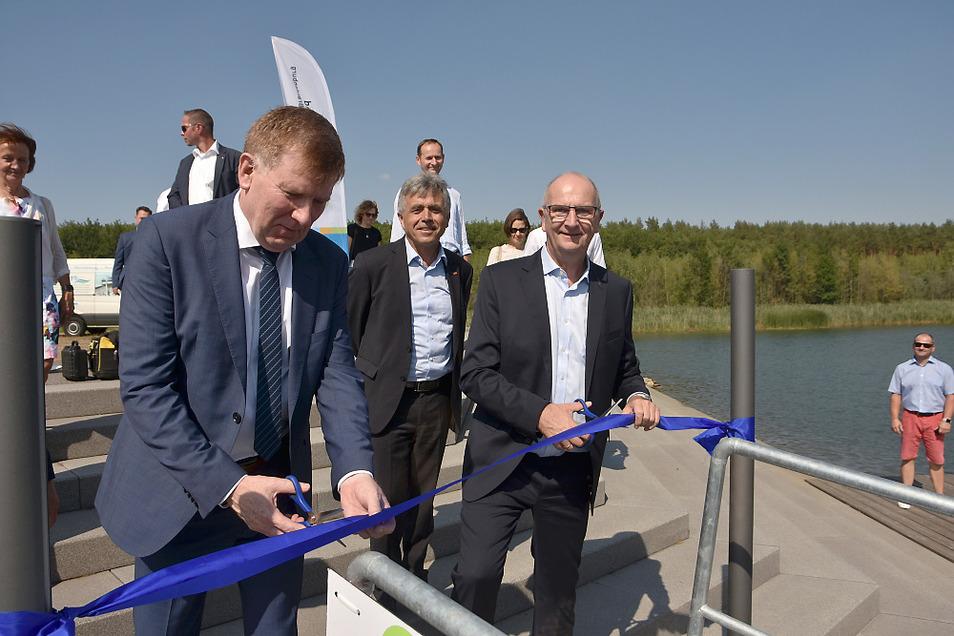 Staatssekretär Frank Pfeil (links) für Sachsen und Ministerpräsident Dietmar Woidke für Brandenburg zerschnitten gemeinsam das Band für die Steganlage am Koschener Kanal.