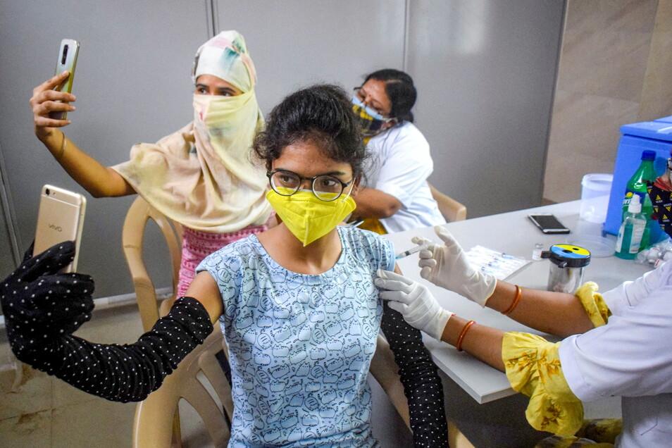 Indien, Allahabad: Zwei Frauen machen Selfies, während sie eine Corona-Impfung erhalten.
